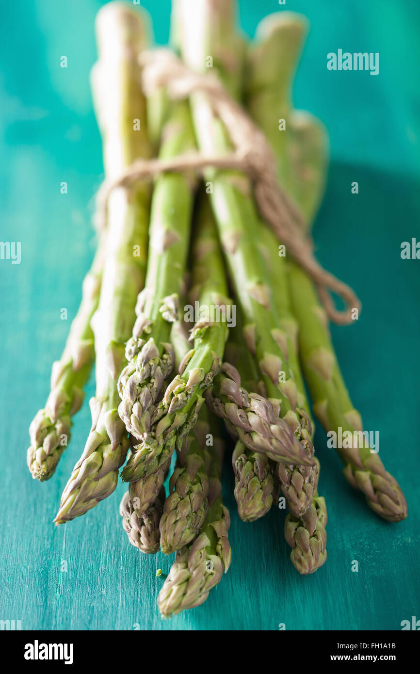 bunch of fresh asparagus on turquoise background - Stock Image