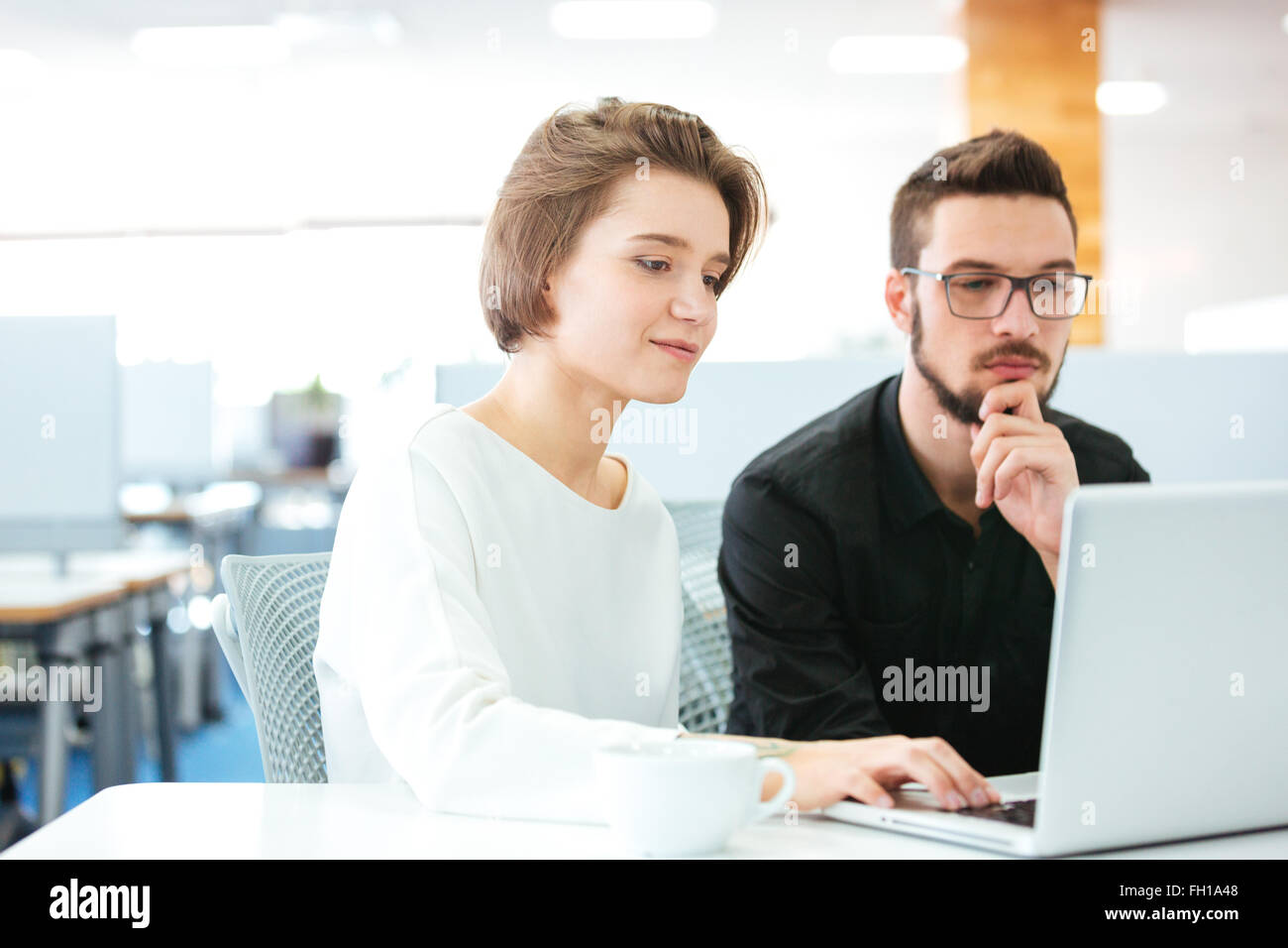 Concentrated young man and woman sitting and discussing new project using laptop in office - Stock Image