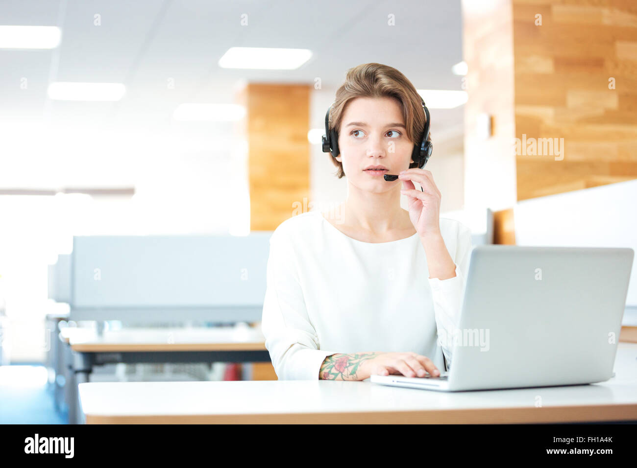 Beautiful young woman in headset sitting and working in call center in office - Stock Image