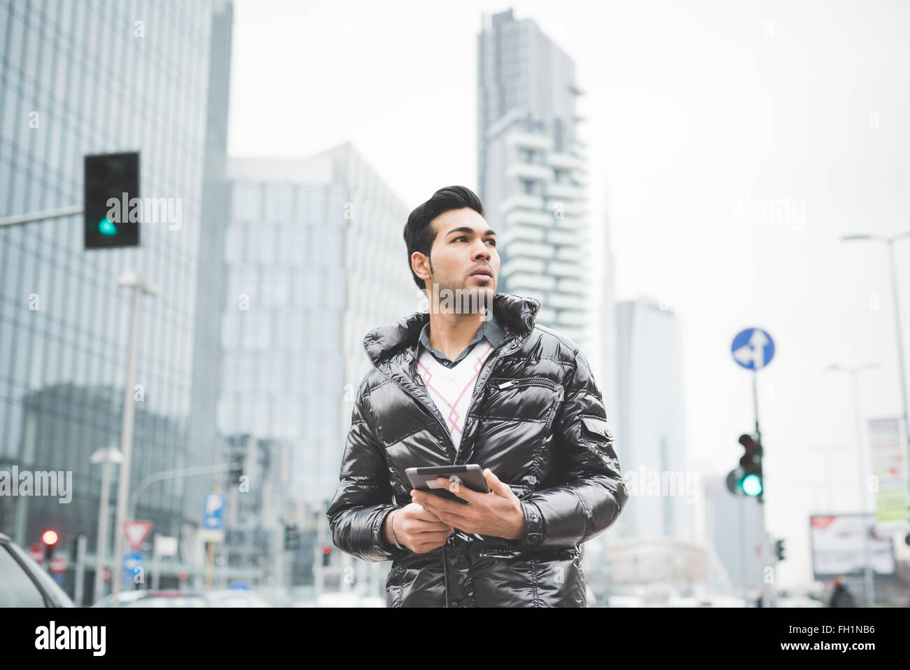 Half length of a young handsome contemporary business man using a tablet in the street of the city overlooking on - Stock Image