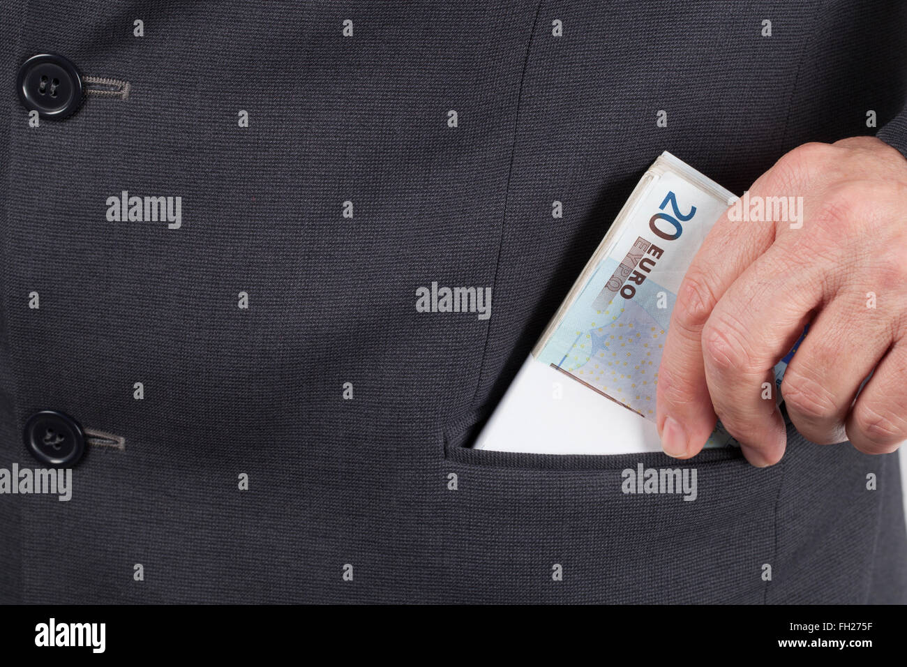 Man in suit putting a wad of twenty Euros banknotes in his pocket. - Stock Image