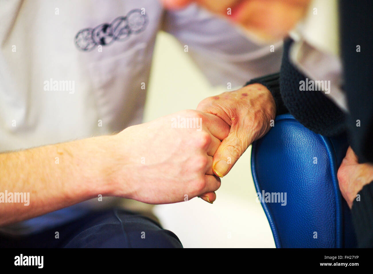 male health care & health visitor holds the hand of an elderly male patient - Stock Image