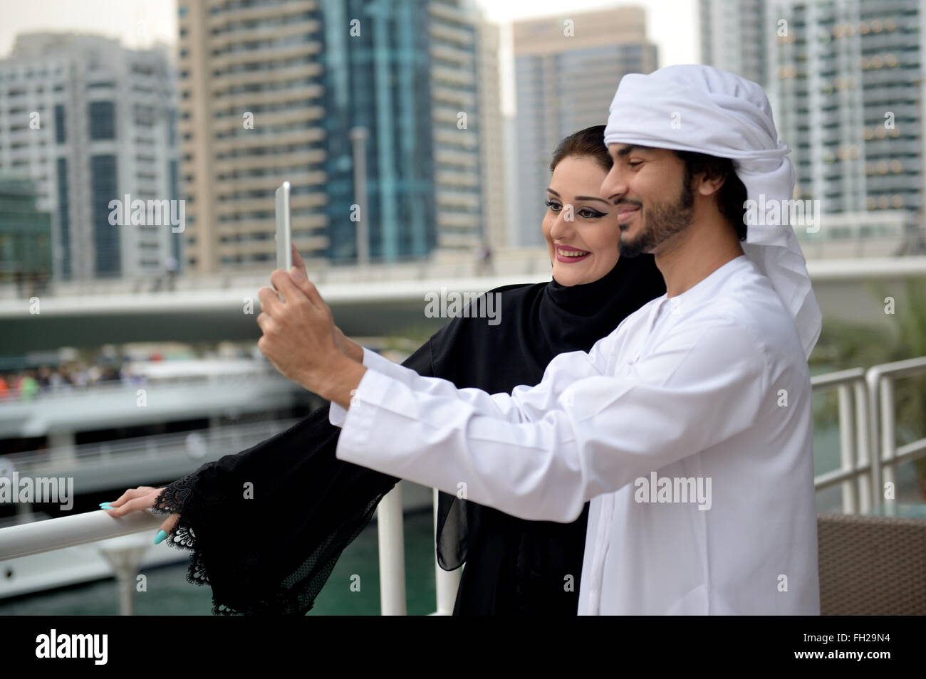 Young Emirati arab couple taking selfie with smartphone Stock Photo