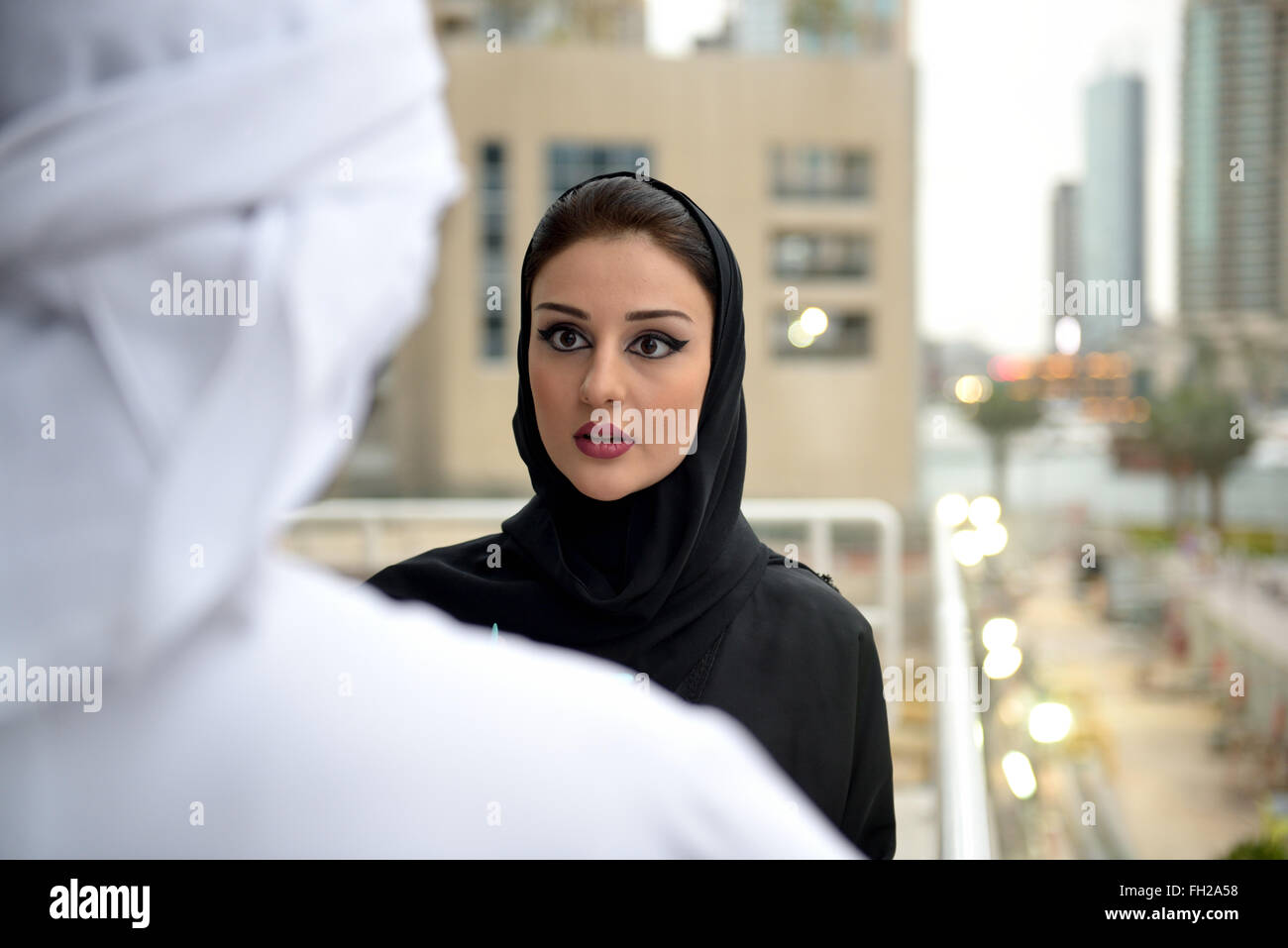 Young Emirati arab couple talking by the canal Stock Photo