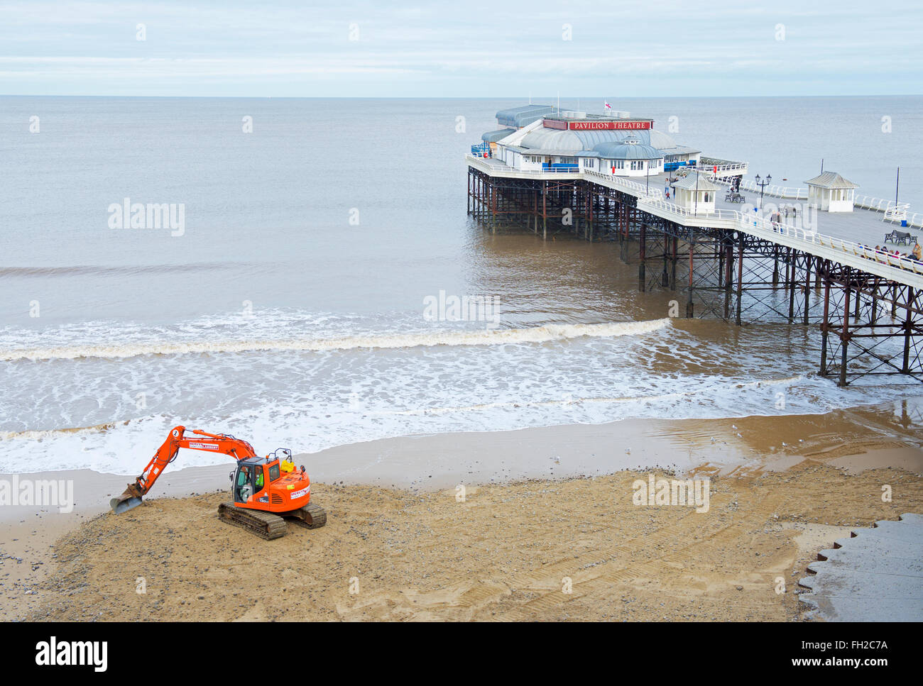 Digger moving sand next to the pier, Cromer, Norfolk, England UK Stock Photo
