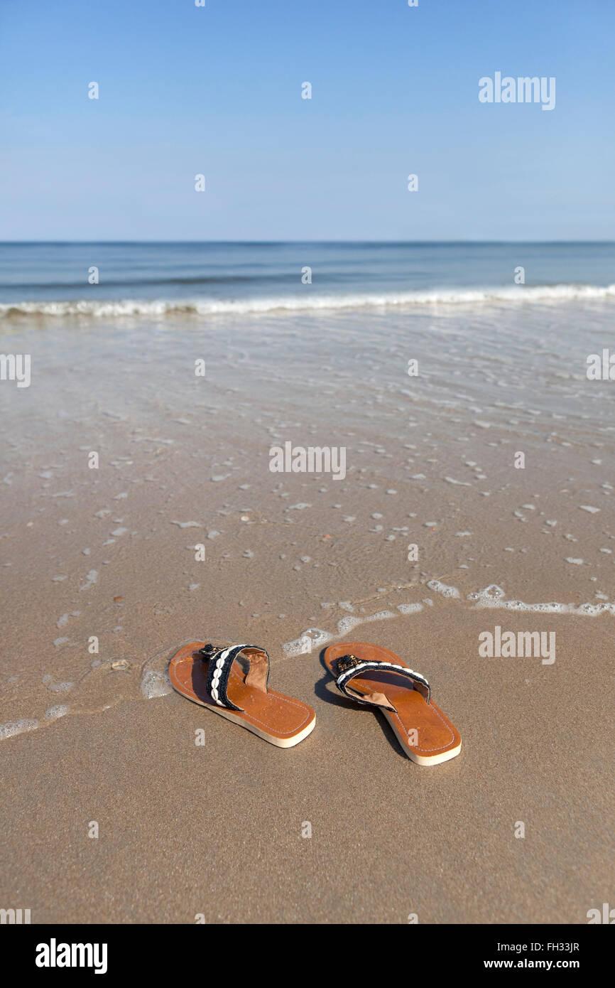 Left slippers on the seaside - Stock Image
