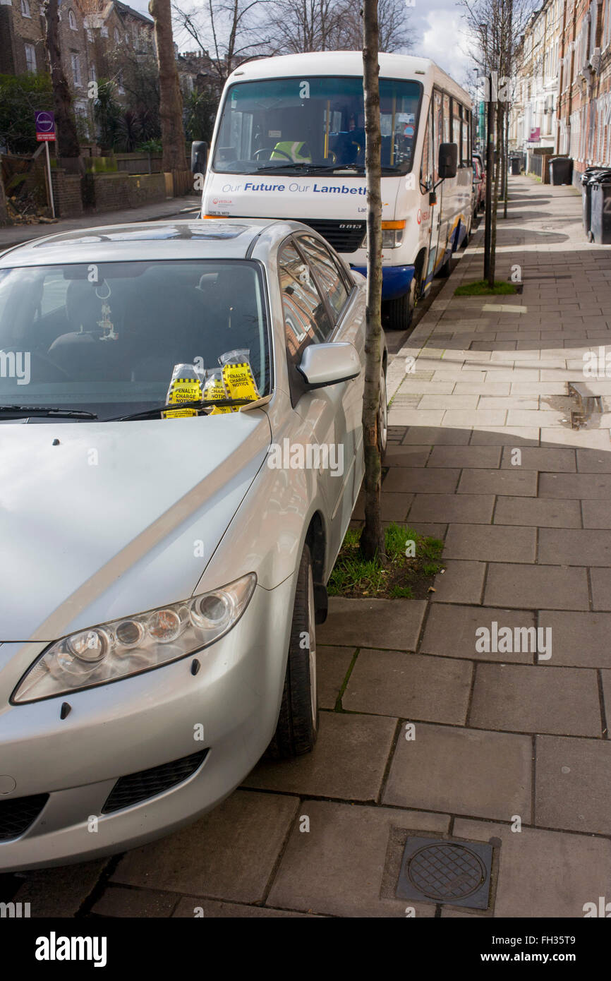 Many penalty charge notices (PCNs) accumulated under the windscreen wiper of a badly-parked car in Brixton, Lambeth, - Stock Image