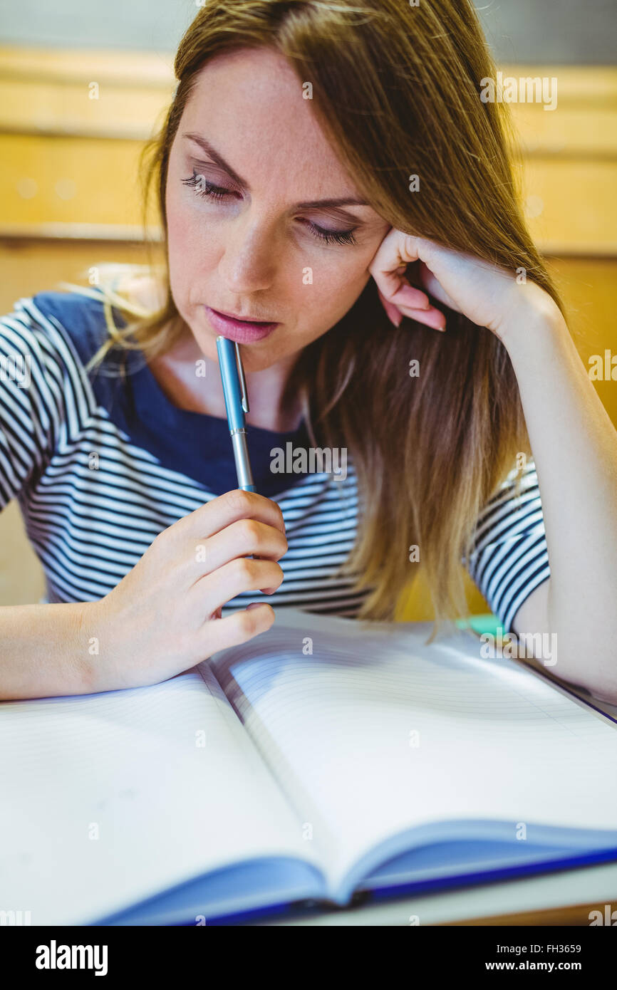 Mature student taking notes in lecture hall - Stock Image
