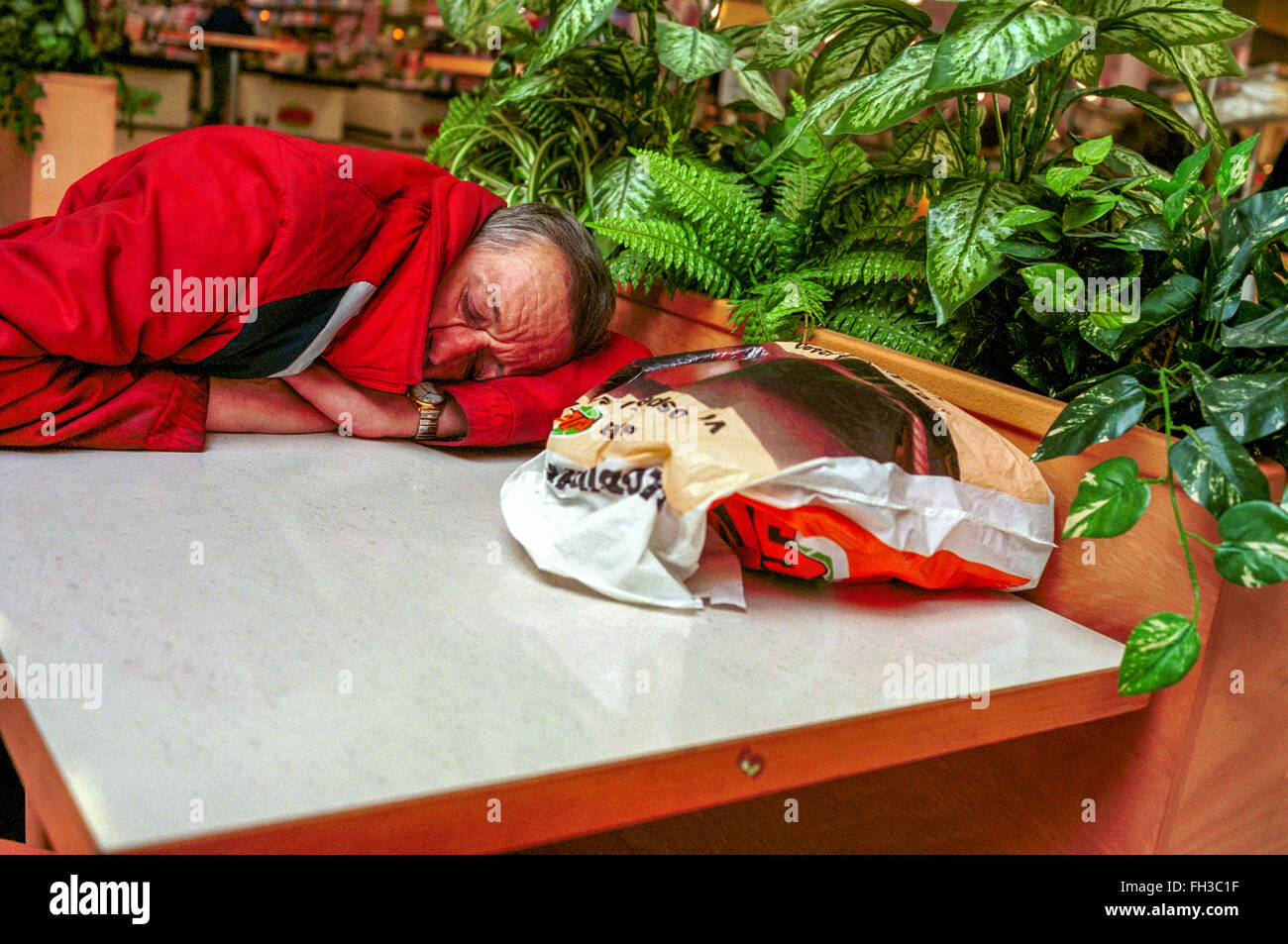 Fatigue old man in a shopping center - Stock Image