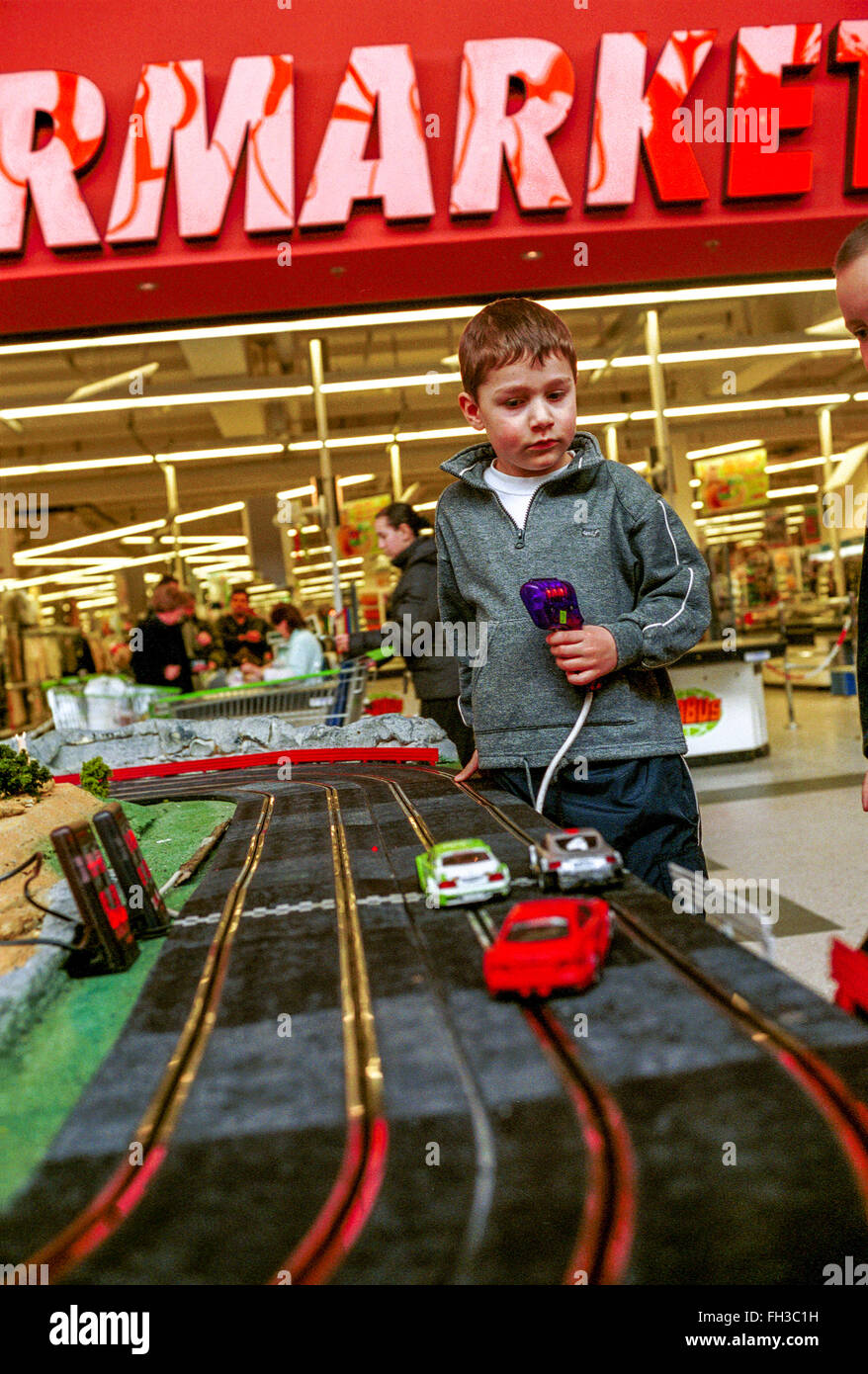 Slot racing car track and playing child, shopping center - Stock Image