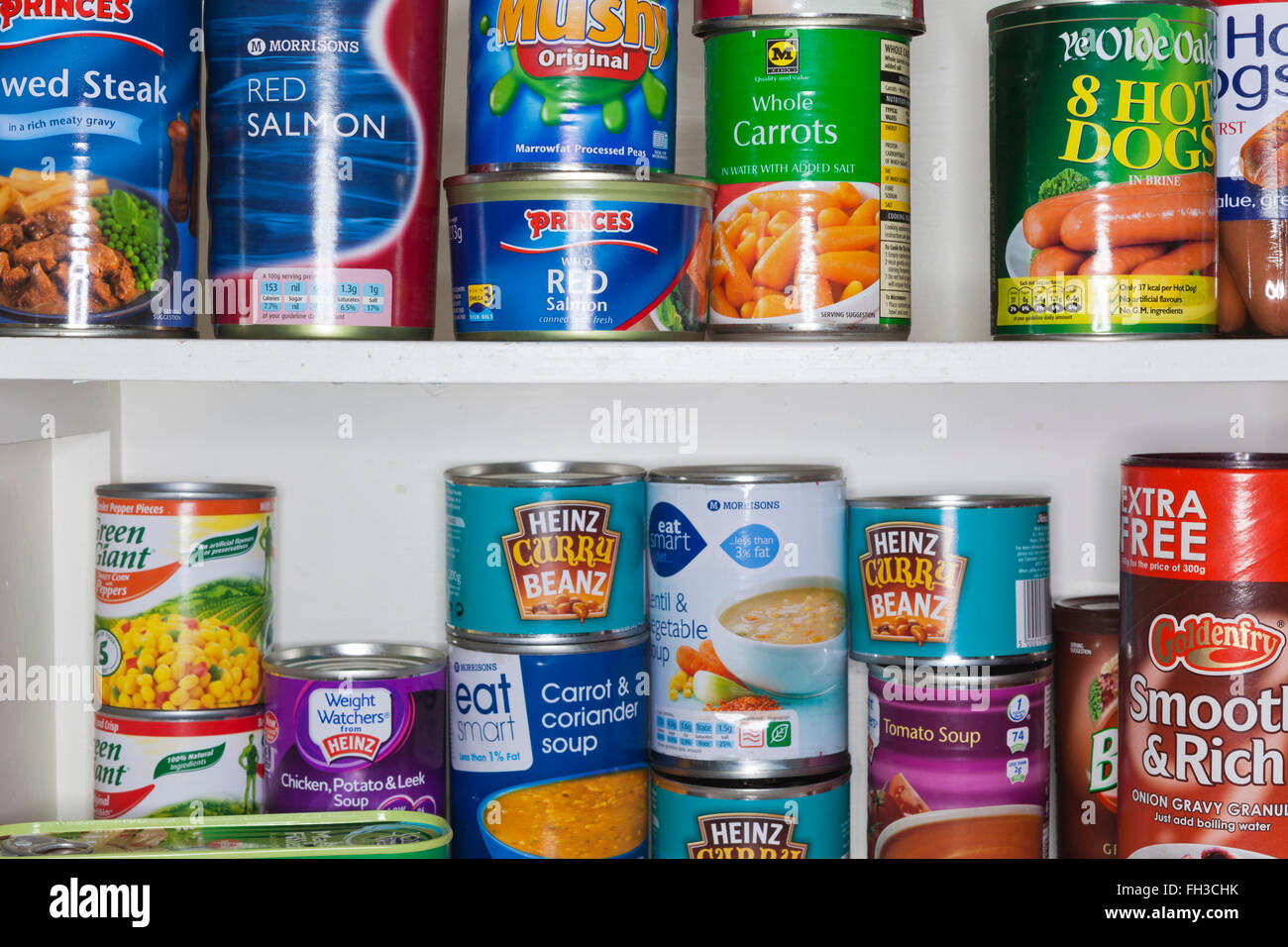 Old glass fronted kitchen cabiinet with tins of food. - Stock Image