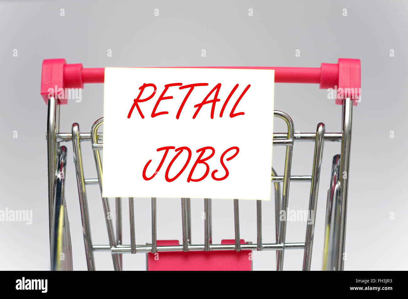 A miniature shopping trolley with retail jobs sign on - Stock Image