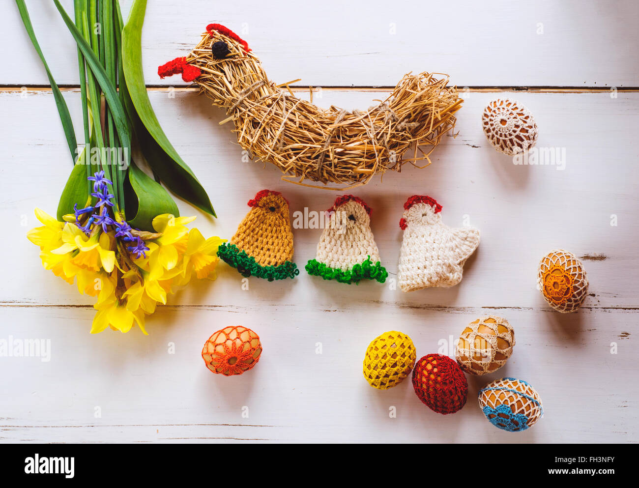 Crocheted Easter eggs, chickens and daffodils, wooden background - Stock Image