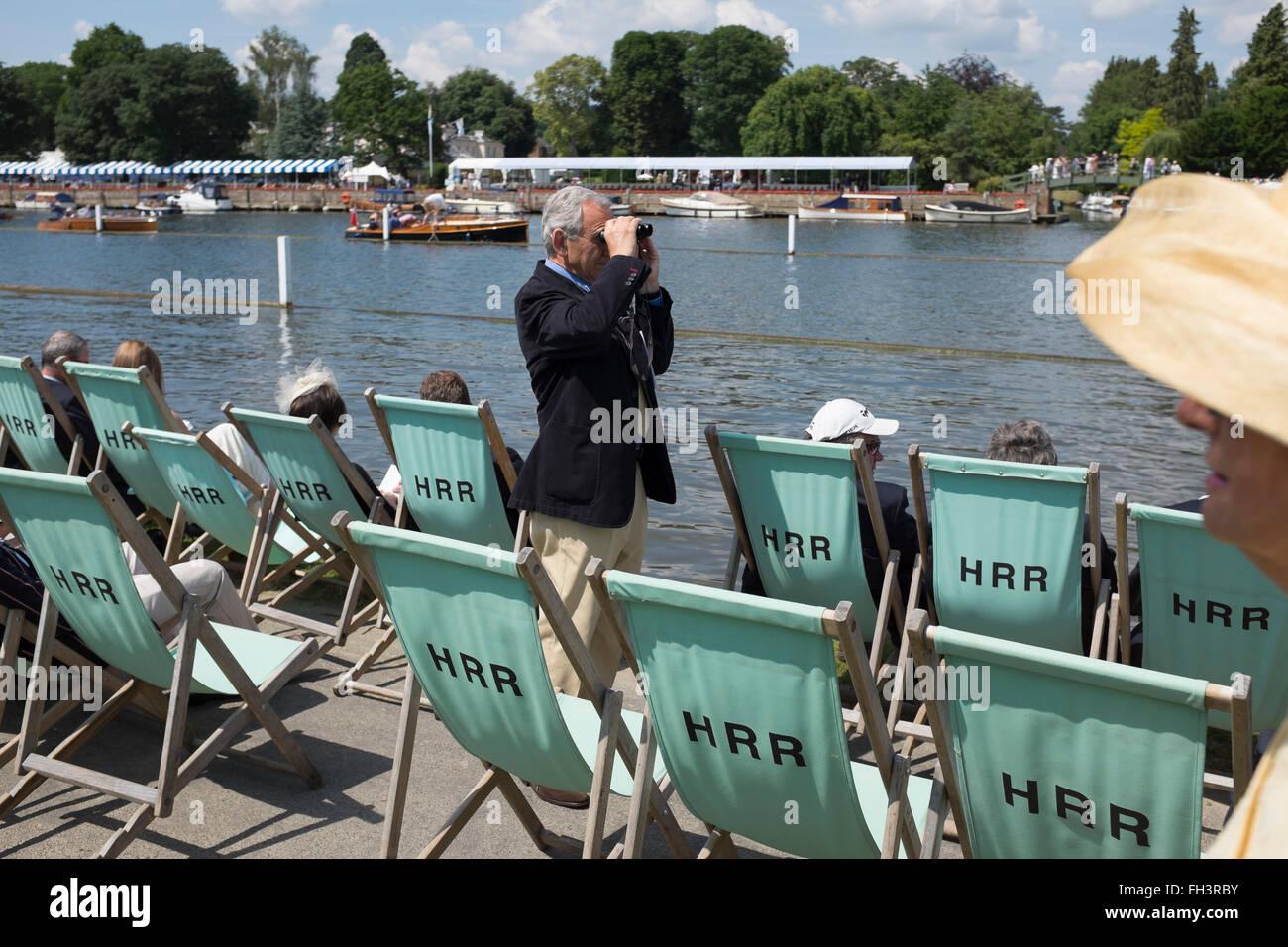 A spectator at Henley Royal Regatta surveys the course. - Stock Image