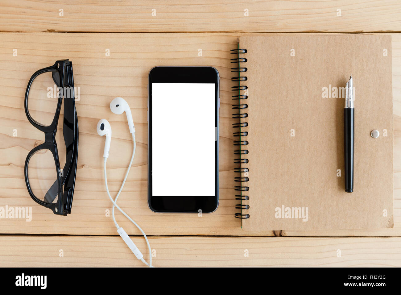 phone white screen on wood workspace top angle view - Stock Image