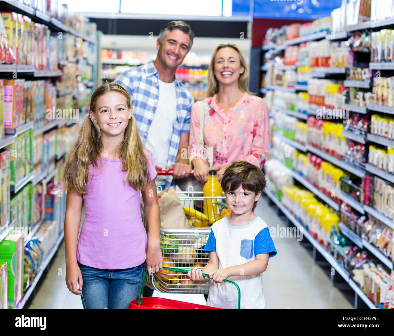 Happy family at the supermarket - Stock Image