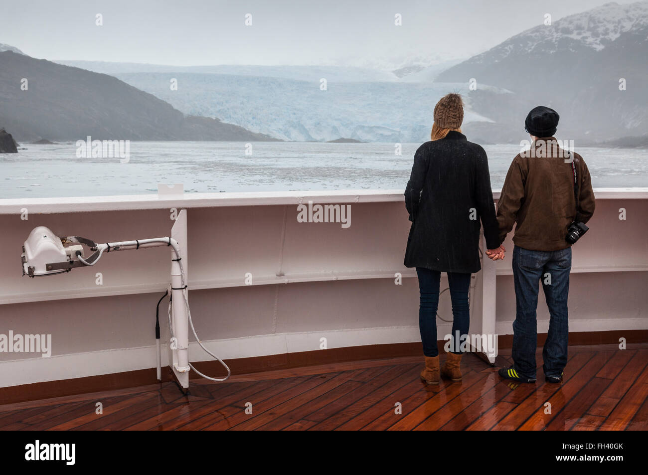 Couple on board the cruise ship Veendam viewing beautiful glacier. - Stock Image