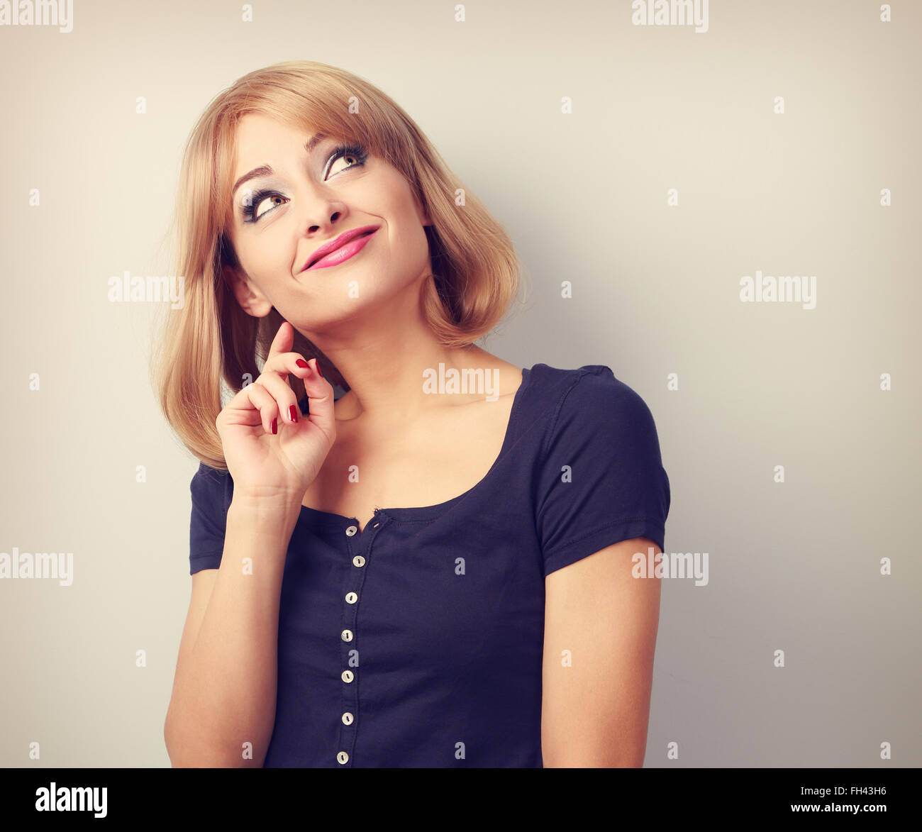 Beautiful funny thinking grimacing young woman looking up. Toned closeup portrait Stock Photo