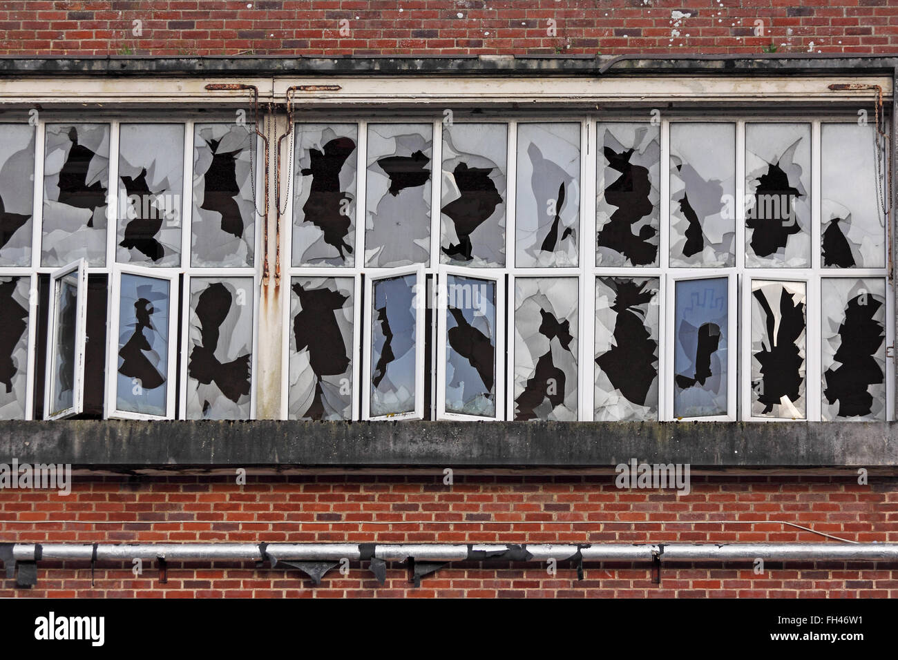 Arrays of shattered window panes in a disused industrial premises UK - Stock Image