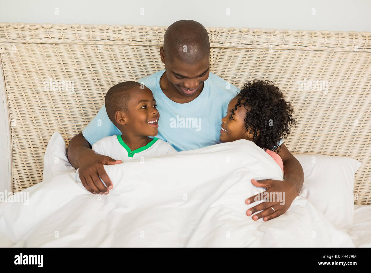 Smiling father in bed with children - Stock Image