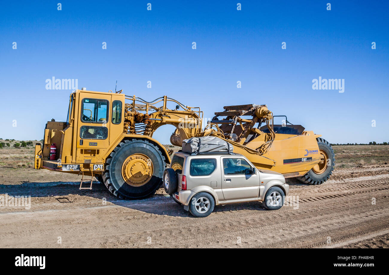 4WD vehicle dwarfed against a huge Caterpillar Motor Scraper outback road maintenance machinery on the New Strzelecki - Stock Image