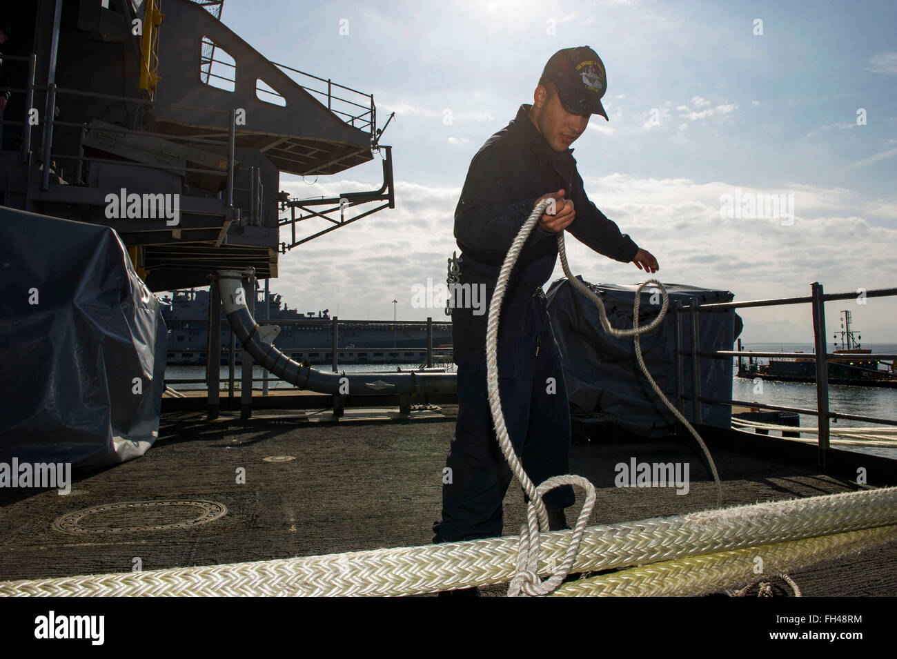 NORFOLK, Va. (Feb. 22, 2016) - Seaman Jason Santamaria fakes out a messenger line on the fantail of the aircraft - Stock Image
