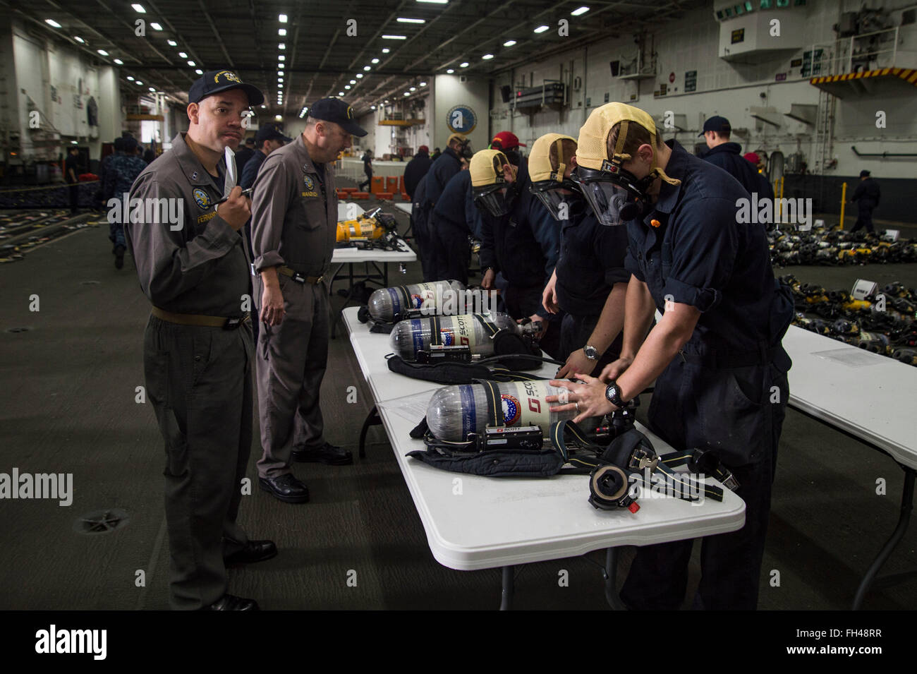 NORFOLK, Va. (Feb. 22, 2016) - Sailors inspect self-contained breathing apparatus bottles and masks in the hangar - Stock Image