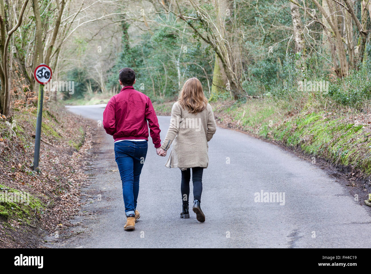 Young couple walk away hand in hand along a tree lined country lane in early Spring, Surrey, England. Stock Photo