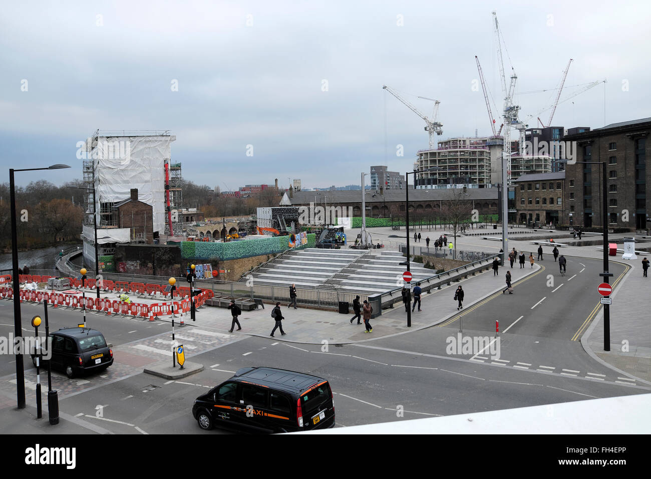 View of Granary Square, Gasholder Apartments and Plimsoll Building cranes King's Cross Regeneration London UK - Stock Image