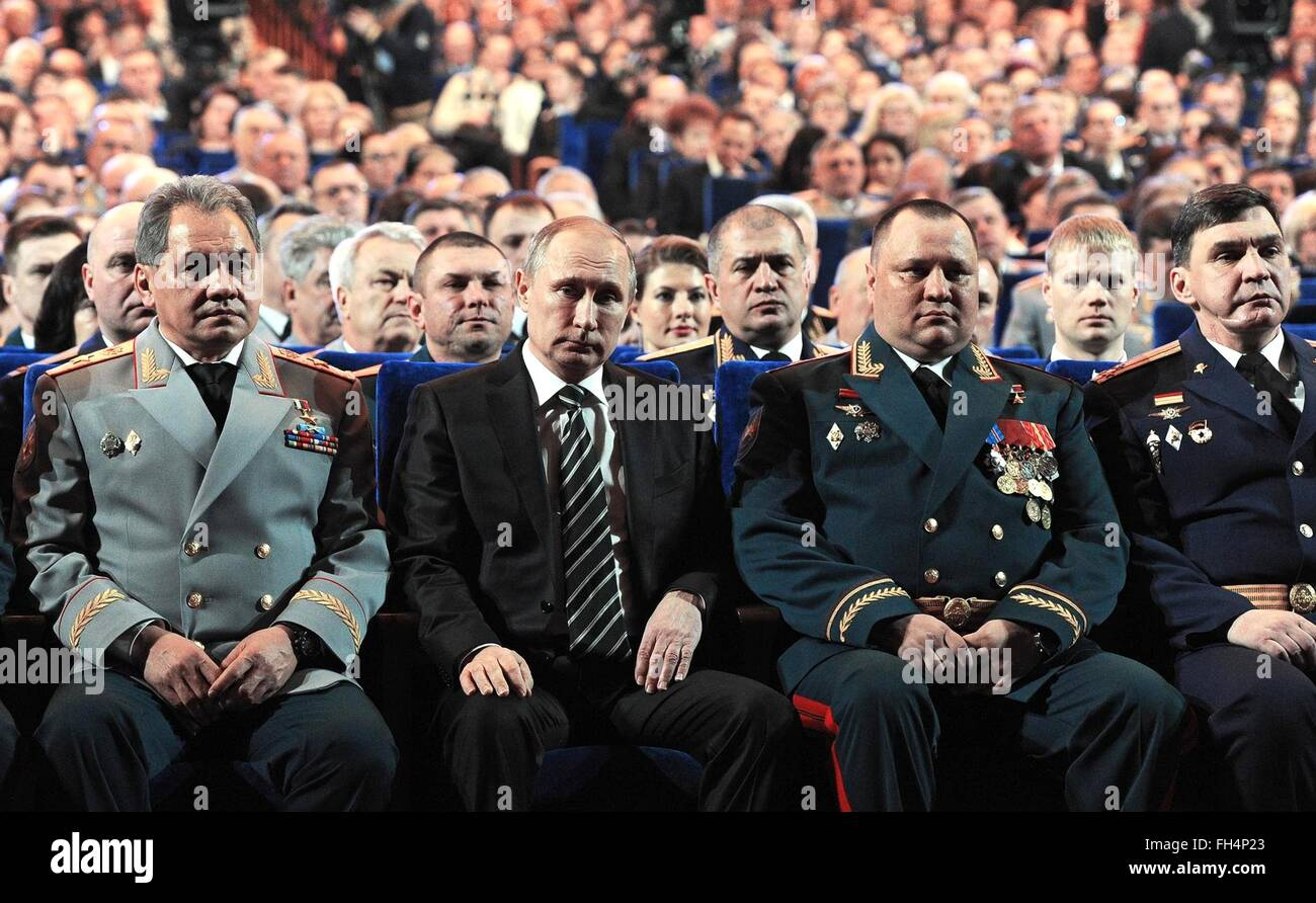 Russian President Vladimir Putin, center, sits with Defence Minister Sergei Shoigu, left, during a concert marking - Stock Image