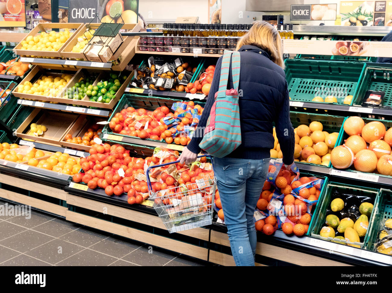 A woman shopping for fruit in Tesco supermarket aisle, Suffolk UK - Stock Image