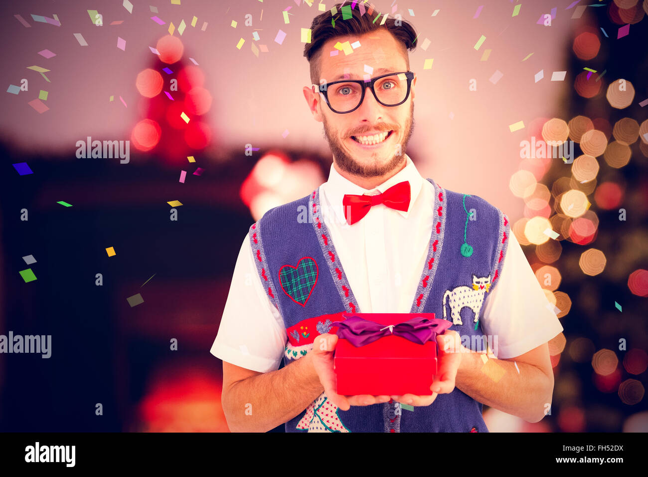 Composite image of geeky hipster offering christmas gift - Stock Image