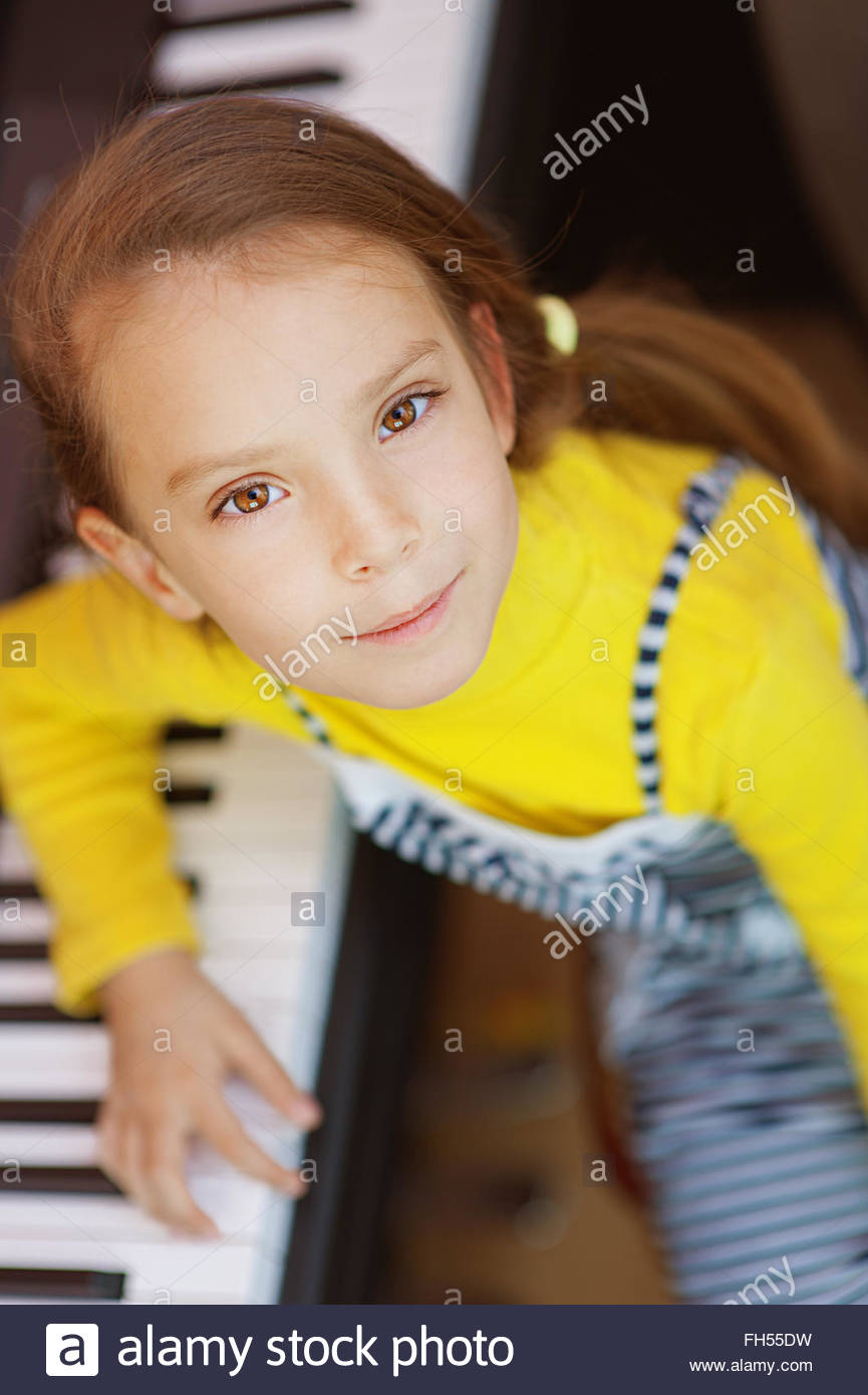 little girl in yellow dress plays piano - Stock Image