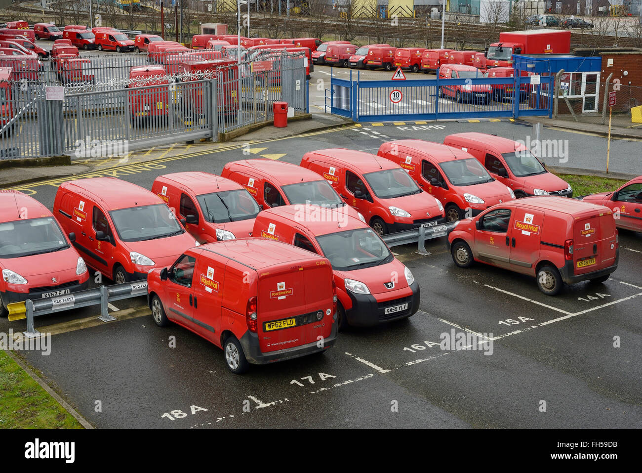 Red Royal Mail delivery vans parked in a sorting office car park - Stock Image