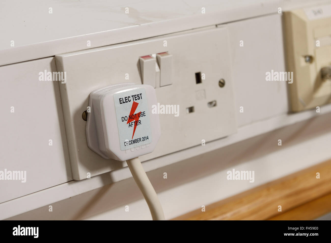 Electrical test sticker on a UK plug and socket - Stock Image