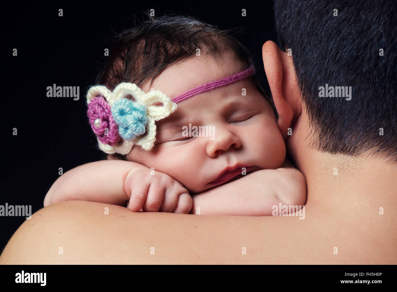 Cute newborn baby girl with knitted headband sleeping on dads shoulder studio black background