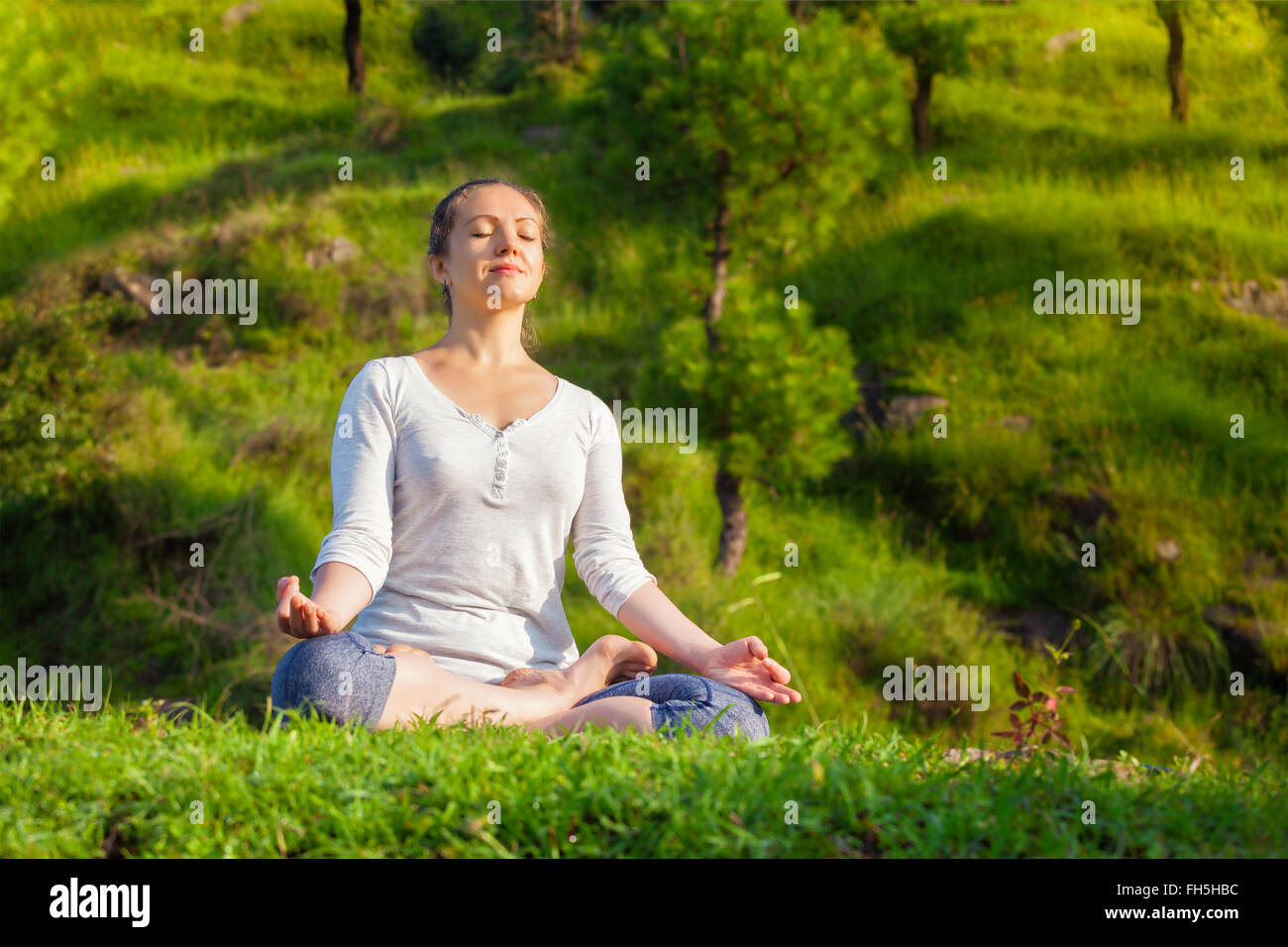 Young sporty fit woman in yoga Lotus pose oudoors - Stock Image