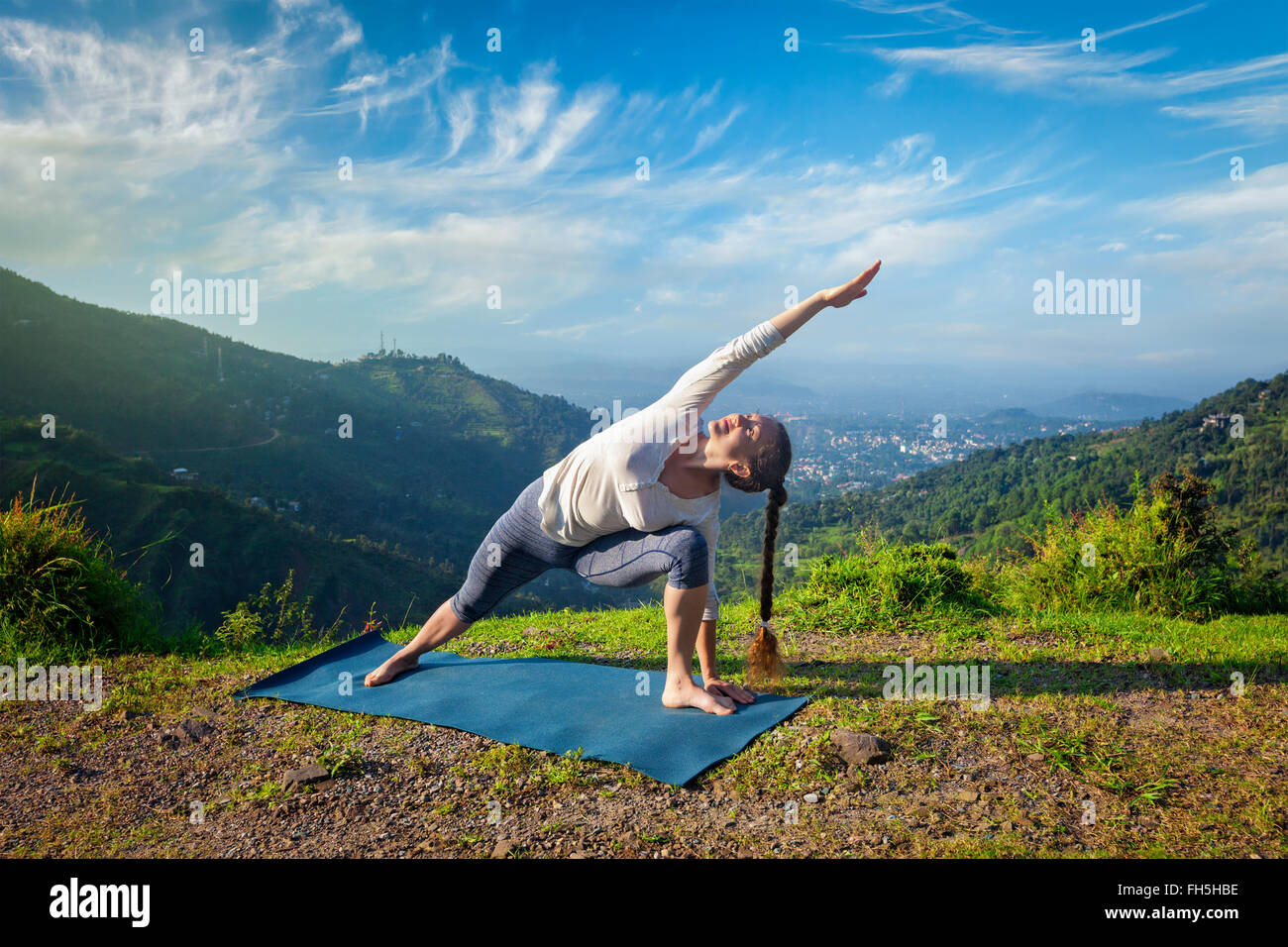 Woman practices yoga asana outdoors - Stock Image