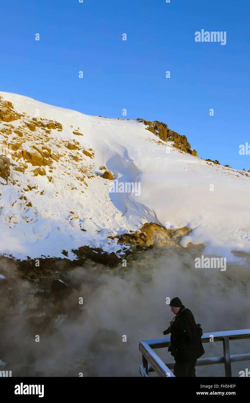 Krýsuvík geothermal area boiling hot spring where tourist on boardwalk engulfed in steam winter Reykjanes - Stock Image