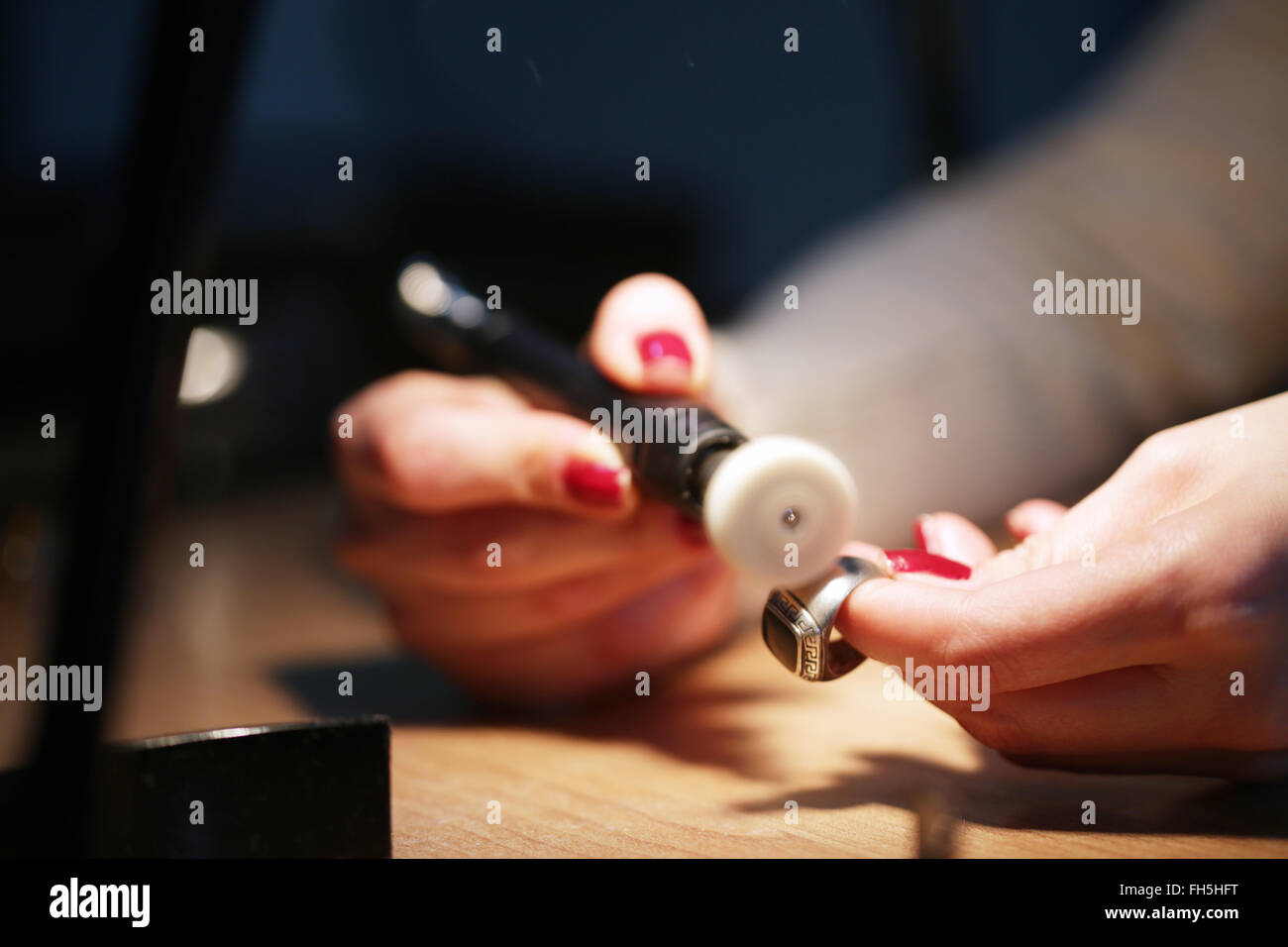 Woman Jeweller prepare a silver ring to polishing - Stock Image