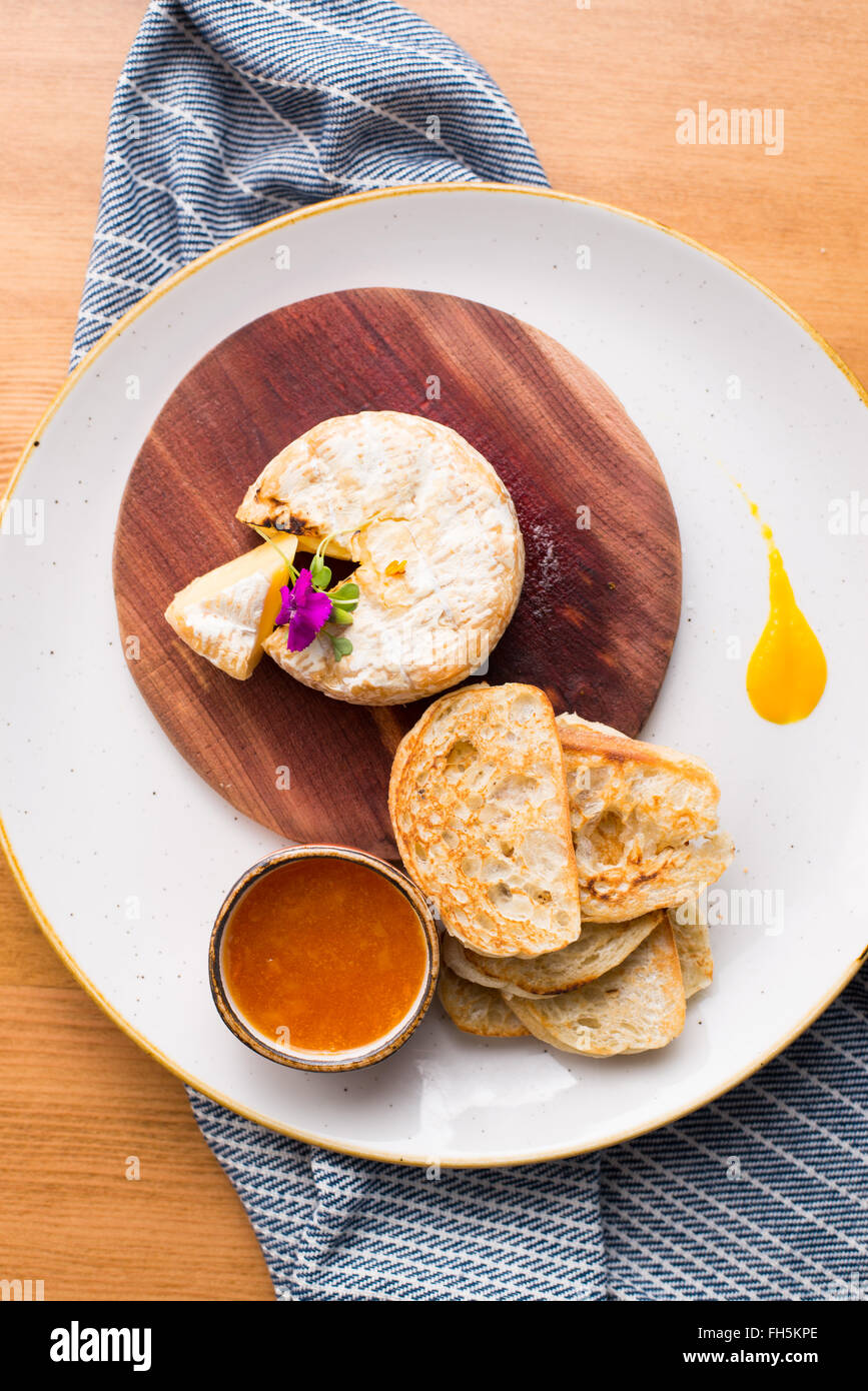 An overhead view of brie cheese with crostini and a red dipping sauce. - Stock Image