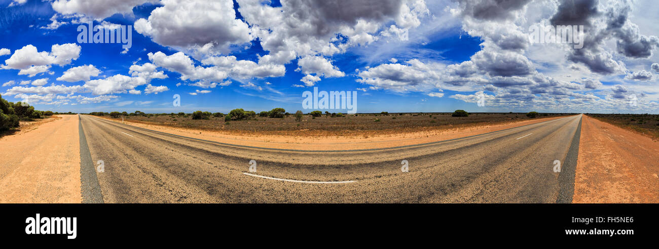 wide panorama of empty eyre highway in Nullarbor plain of South Australia on a sunny summer day. Stock Photo
