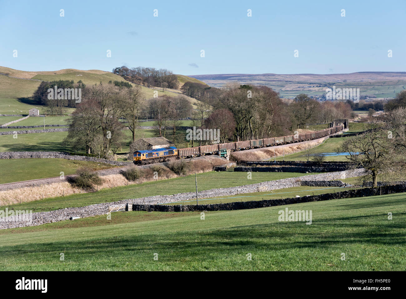 A minerals train from Swinden Quarry passes Cracoe near Grassington in the Yorkshire Dales National Park, UK. - Stock Image
