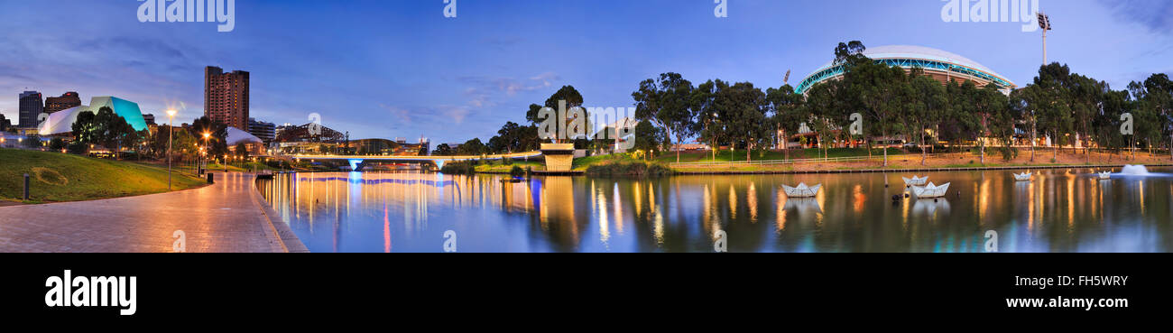 panorama of Adelaide city centre over Torrens river at sunrise. From CBD high-rises to oval in public park with - Stock Image