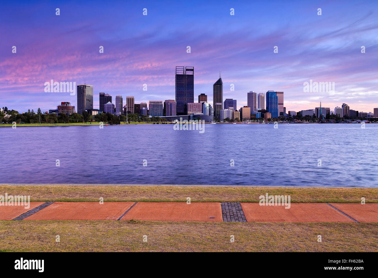 panoramic view of skyscrapers in Perth, Western Australia, across Swan river at sunrise. Walking trail in background. - Stock Image