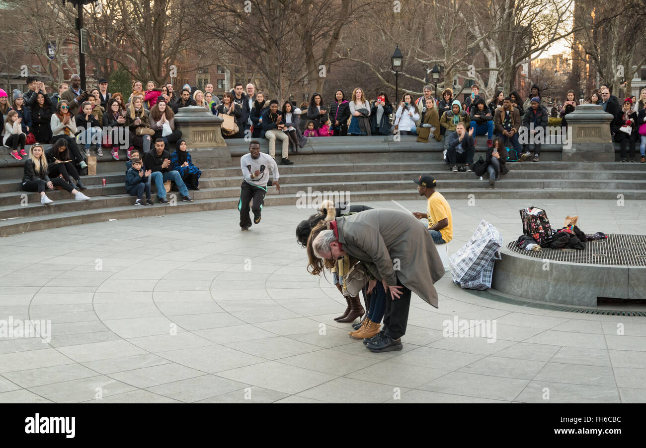 Street performance in Washington Square Park of acrobat somersaulting over volunteers with crowds of spectators Stock Photo
