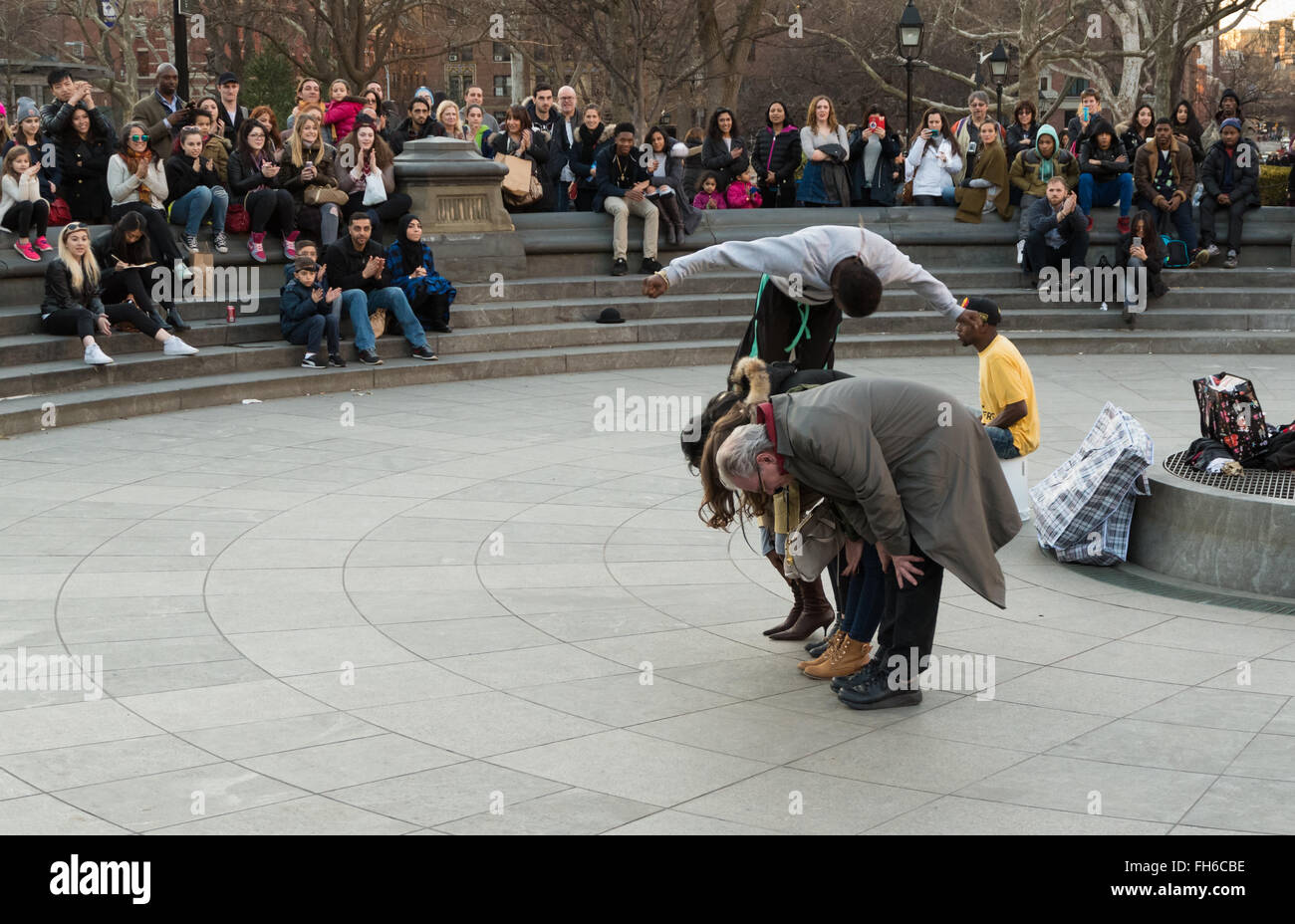 Street performance in Washington Square Park of acrobat somersaulting over volunteers with crowds of spectators - Stock Image