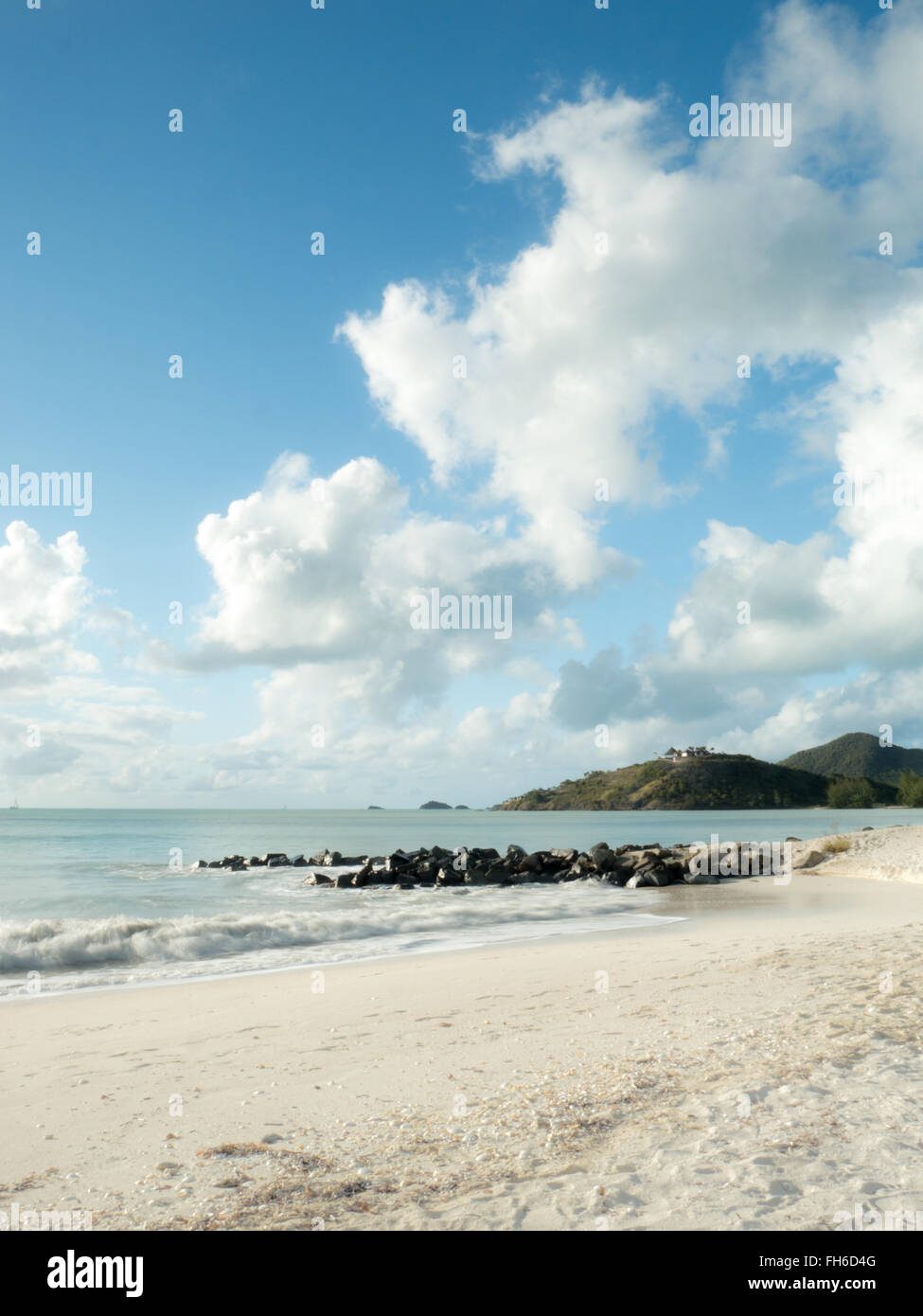 Caribbean beach scenery with turquoise water and hills in the background - Stock Image