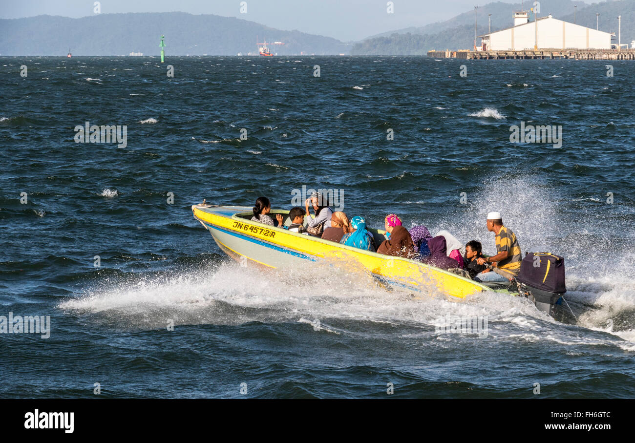 Boats going to and from the Island around Kota Kinabalu Sabah Malaysia when the sea is rough on an otherwise fine - Stock Image