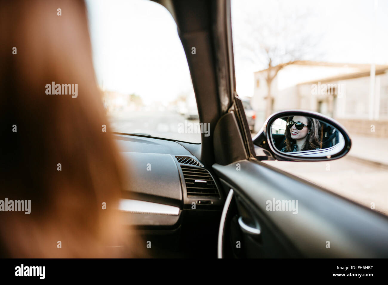 Female front passanger in car reflected in car mirror - Stock Image